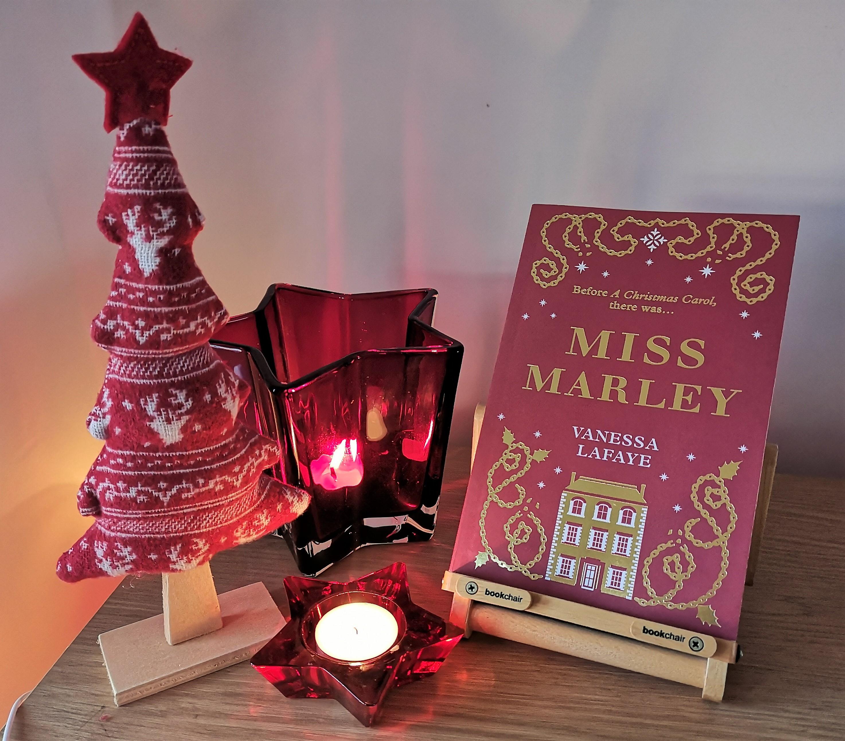 A photo of the book Miss Marley along with some Christmas candles and a nordic Christmas tree.