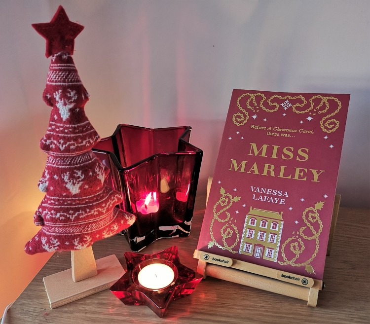 A photo of the book Miss Marley with some christmas items, including christmas candles and a mini nordic christmas tree.