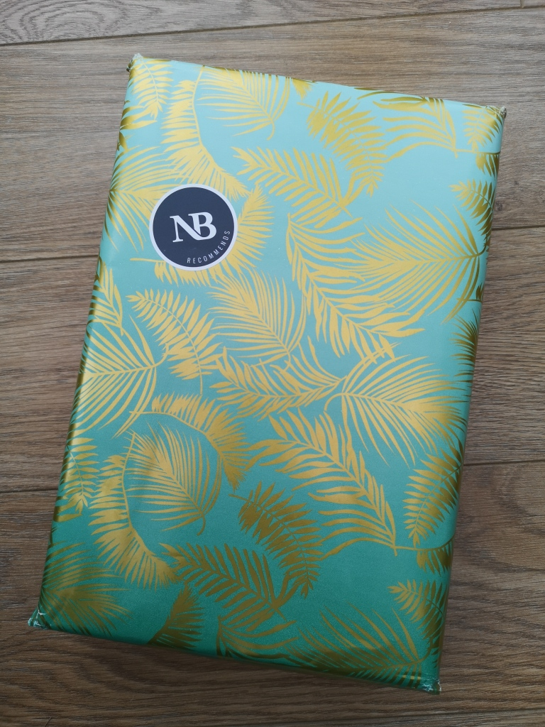 A picture of a wrapped parcel. The wrapping paper is a green-blue colour with gold ferns. There is a sticker on the parcel which reads NB Recommends. The parcel is on a wooden floor.