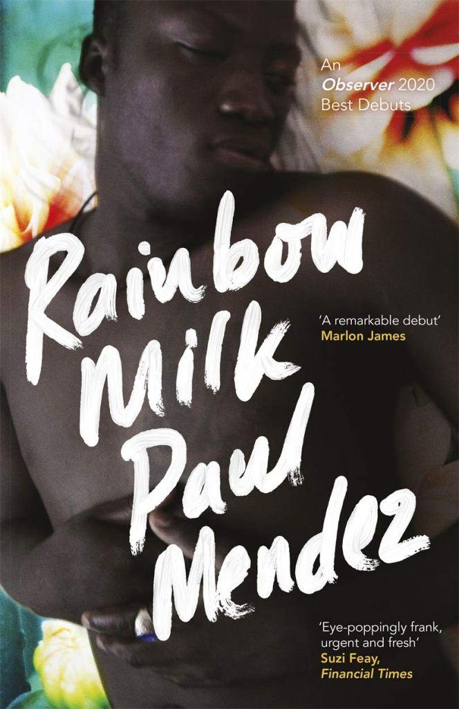 This is the book cover of Rainbow Milk by Paul Mendez. It shows a man laying on a bed, he is topless and appears to be asleep. The name of the book is in white on top of him.